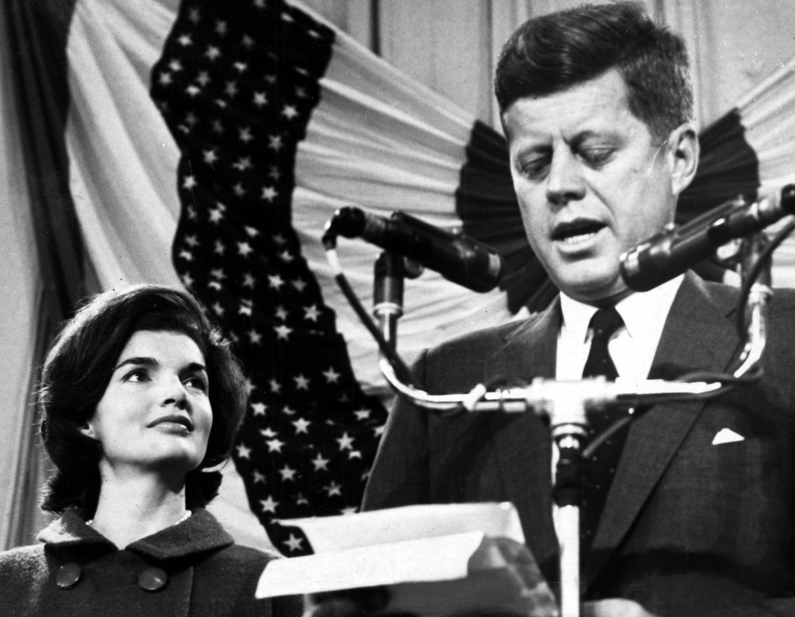 President-elect John F. Kennedy and his wife Jacqueline standing at the podium inside the Hyannis Armory, November 9, 1960.